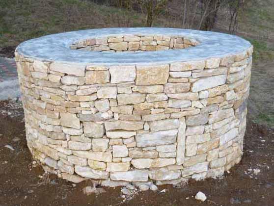 Photo d'un puits en pierre, dans un jardin