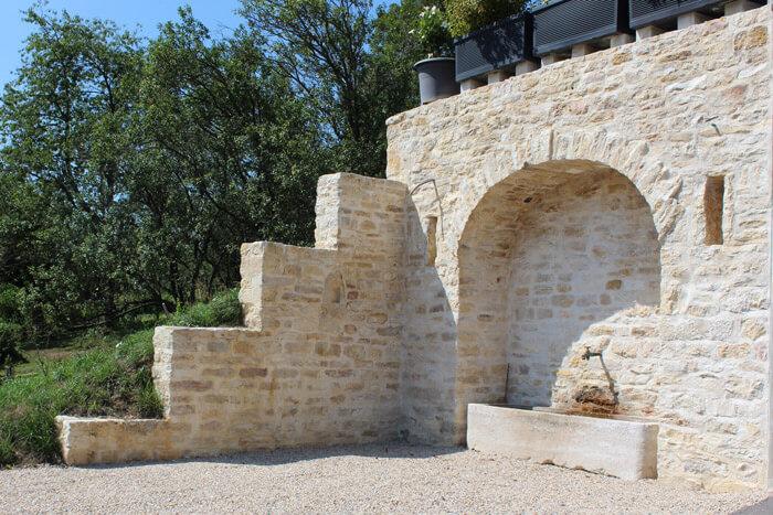 Photo mur en pierre avec voute et fontaine